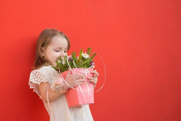 Pequeña dama de honor adorable sosteniendo flores