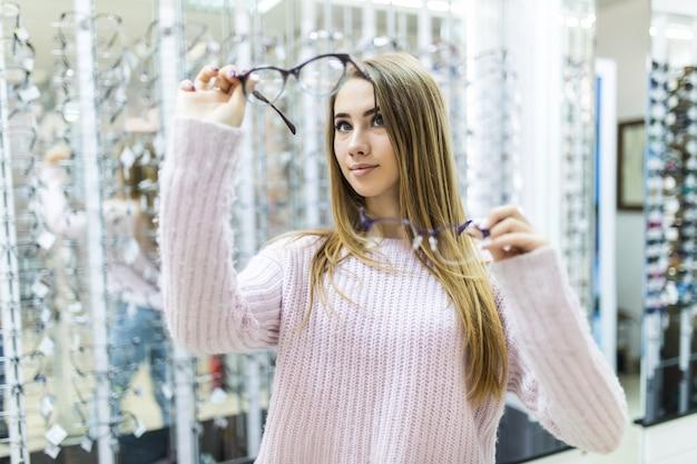 Pequeña dama vestida con un suéter blanco sostiene anteojos médicos en su brazo y mira a través de ellos en una tienda especial