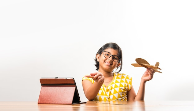 Pequeña estudiante india que hace o mide las alas de un avión de papel o un avión, hace un proyecto escolar o aprende ciencias con un tutorial en línea