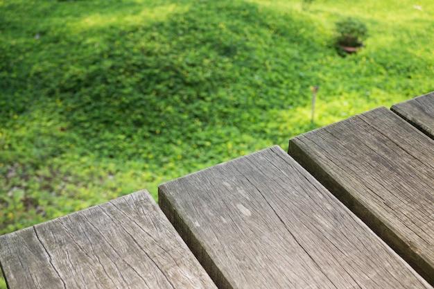 Pequeña flor amarilla en hierba verde con el fondo de madera