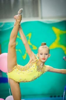 Pequeña gimnasta bella y activa en competiciones de gimnasia rítmica