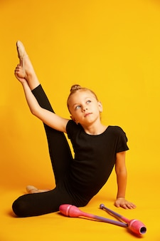 Pequeña gimnasta estirando la pierna cerca de las varitas durante el entrenamiento