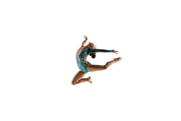 Pequeña gimnasta femenina flexible aislada en la pared blanca