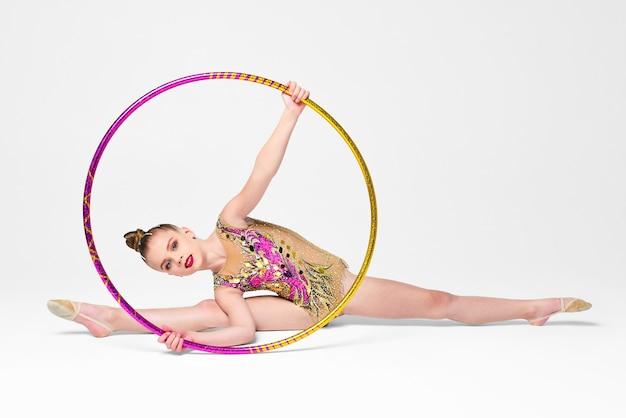 Pequeña gimnasta en un leotardo con lentejuelas realiza un ejercicio con un aro sobre fondo blanco.