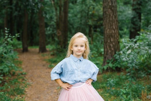 Una pequeña gril rubia en el bosque sostiene sus manos en su cintura y sonríe fácilmente