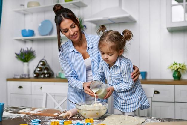 Pequeña y hermosa hija ayuda a mamá a verter leche en la masa