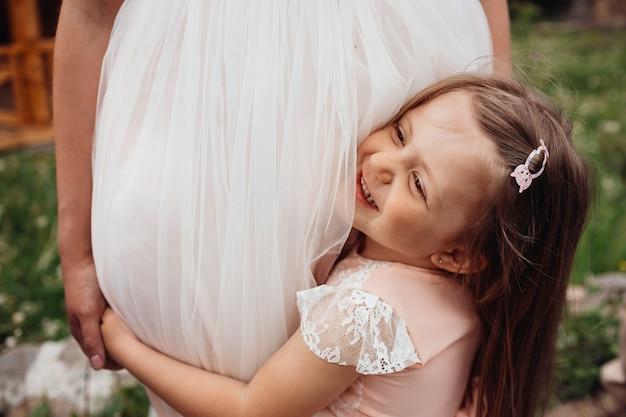 La pequeña hija abraza las piernas de mon