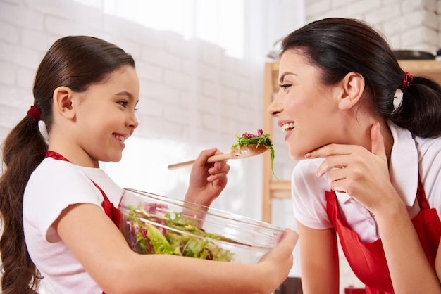La pequeña hija está alimentando a la madre en cocina.