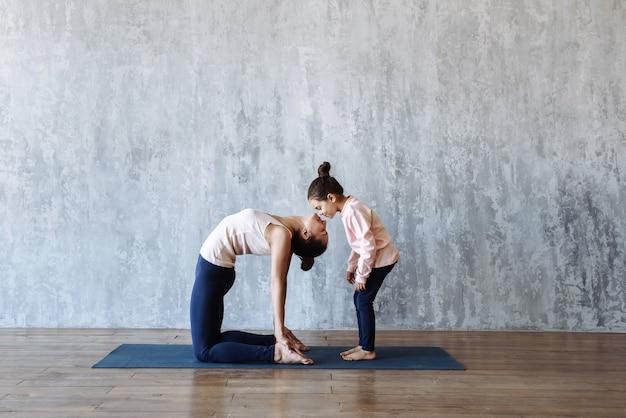 Pequeña hija besando a mamá haciendo yoga en el gimnasio en la colchoneta contra la escena de la pared, amor en la familia