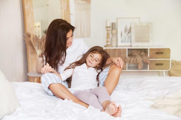 Pequeña hija durmiendo en los brazos de su madre en una cama en un escandinavo