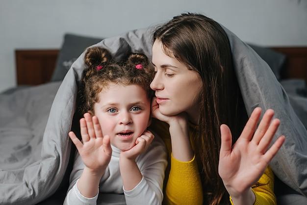 La pequeña hija linda del niño y la joven madre alegre acostada en la cama cubierta con una manta hacen una llamada en línea distante vlog disparando mirando a la cámara hablando por la cámara web, riendo divirtiéndose en casa