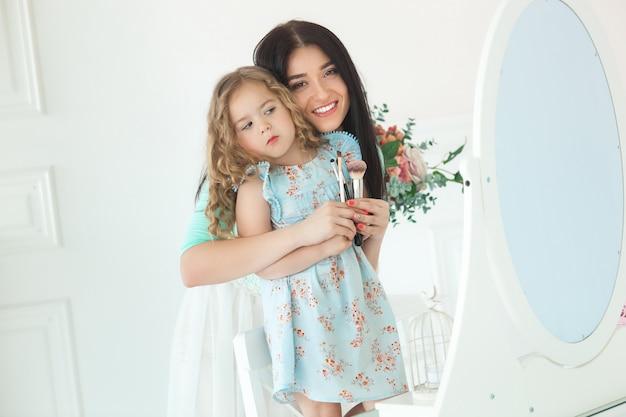 Pequeña hija linda y su madre aplicando se componen. madre bastante joven y adorable niña divirtiéndose juntos. hermosa familia fashionista