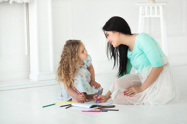 Pequeña hija linda y su madre dibujando con lápices de colores y divirtiéndose juntos. niño bonito y mamá jugando en el interior. familia feliz pasar tiempo dibujando.