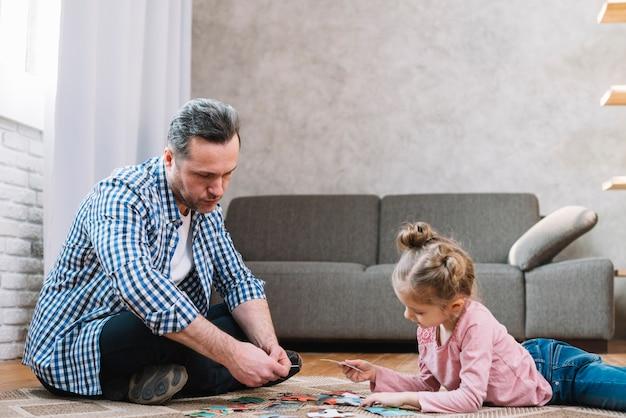 Pequeña hija y padre jugando rompecabezas en casa