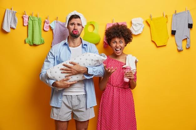 La pequeña hija recién nacida duerme cómodamente en el abrazo de los padres. pareja cansada se preocupa por el bebé. papá molesto con pañal en la cabeza, sostiene al bebé envuelto con una manta. madre irritada va a alimentar a un niño