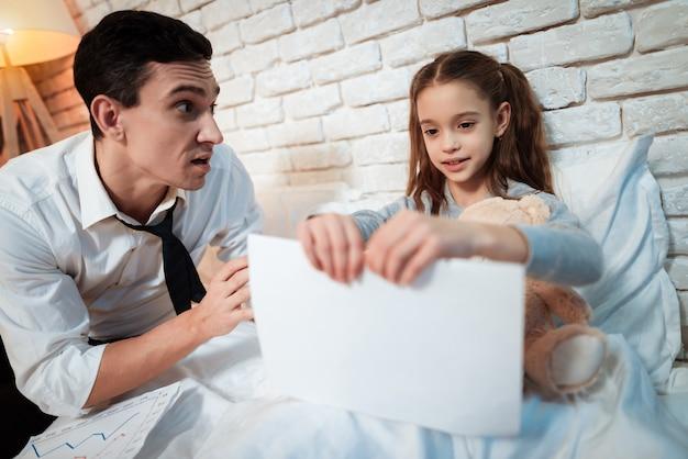 La pequeña hija está rompiendo los papeles de su padre.