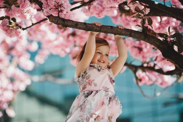 La pequeña hija sostiene una rama del árbol rosado floreciente