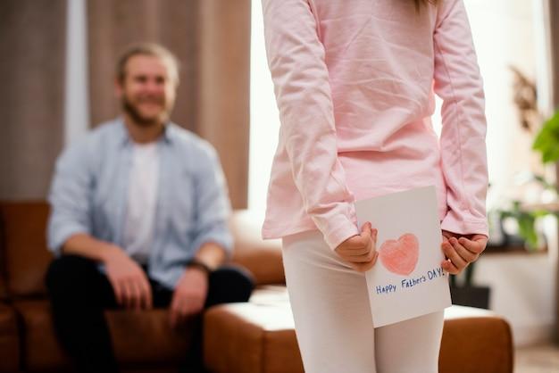 Pequeña hija con tarjeta para el día del padre