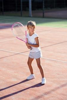 Pequeña jugadora de tenis en uniforme blanco, concentrándose y centrándose en el entrenamiento antes del juego. fondo de luz solar.