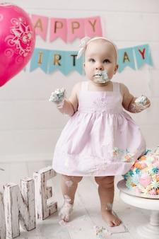 La pequeña y linda niña con vestido rosa se ensucia en crema de pastel para celebrar las vacaciones