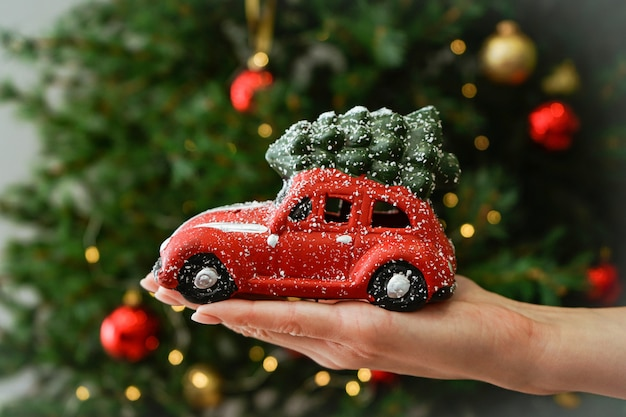 Pequeña máquina roja en una mano femenina en el árbol de navidad.