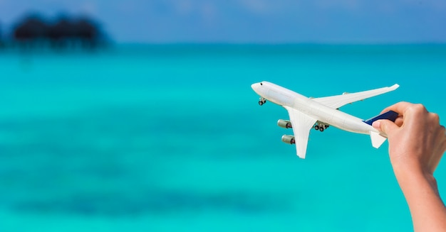 Pequeña miniatura blanca de un avión en el fondo del mar turquesa