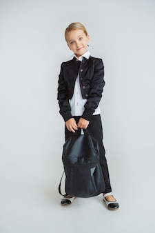 Pequeña modelo femenina posando en uniforme escolar con mochila en la pared blanca