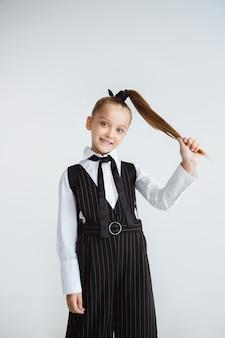 Pequeña modelo femenina posando en uniforme escolar en la pared blanca del estudio