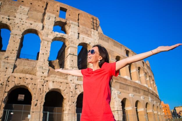 Pequeña muchacha activa adorable con el mapa delante de colosseum en roma, italia.