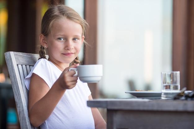 Pequeña muchacha adorable que bebe té en el desayuno en café al aire libre