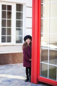 Pequeña muchacha alegre que se coloca cerca de la cabina de teléfono roja en un abrigo y una boina de borgoña. cabina telefónica roja de londres. primavera.