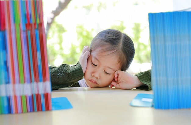 Pequeña muchacha asiática cansada que miente en el estante en la biblioteca.