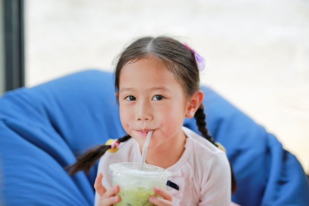 Pequeña muchacha asiática feliz del niño que bebe el té verde helado de matcha que miente en el sofá en el café.
