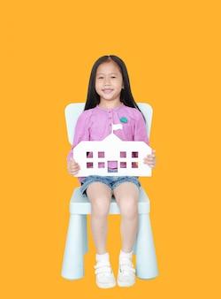 Pequeña muchacha asiática feliz del niño que sostiene la escuela de papel que se sienta en silla del niño