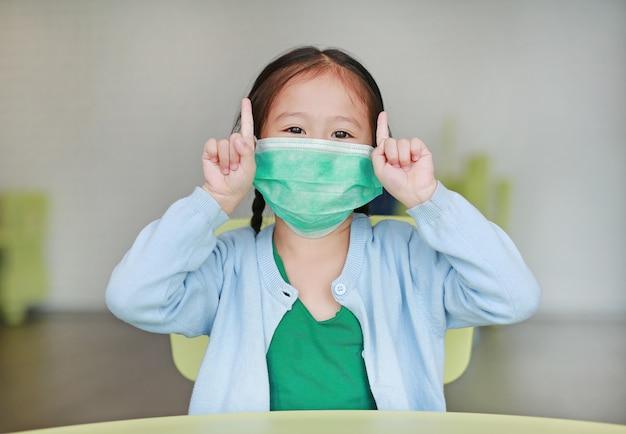 Pequeña muchacha asiática linda del niño que lleva una máscara protectora