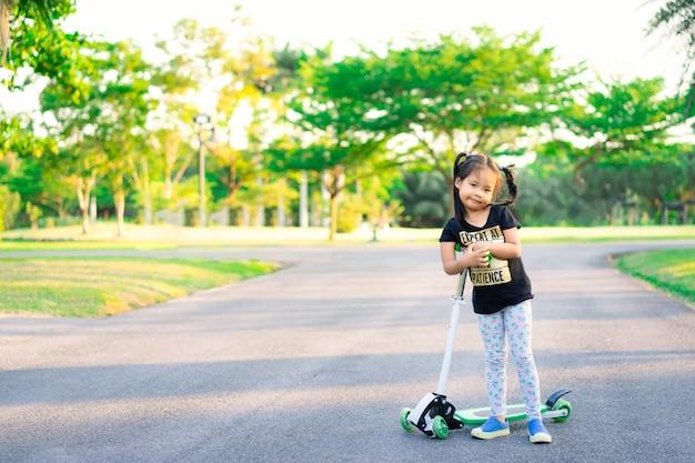 Pequeña muchacha asiática linda que aprende montar una vespa en un parque