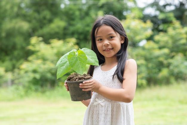 Pequeña muchacha asiática que celebra una planta en el parque