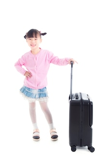 Pequeña muchacha asiática que se coloca con la maleta de la rueda y sonríe sobre el fondo blanco