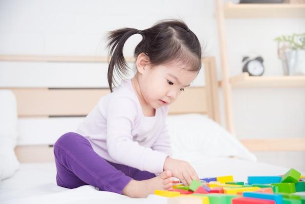 Pequeña muchacha asiática que se sienta en cama y que juega los juguetes en casa