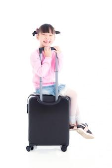 Pequeña muchacha asiática que se sienta en la maleta de la rueda y sonríe sobre el fondo blanco