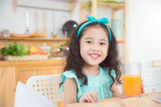 Pequeña muchacha asiática que sonríe mientras que bebe el zumo de naranja en la mesa de desayuno por la mañana