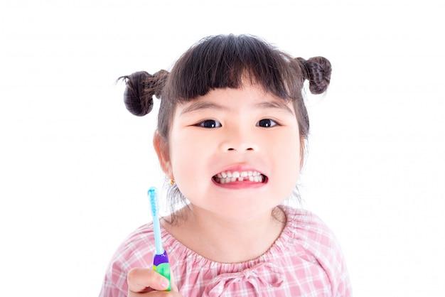 Pequeña muchacha asiática que sostiene el cepillo de dientes y sonrisas sobre el fondo blanco