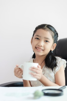 La pequeña muchacha asiática que sostiene la taza blanca y la sonrisa con felicidad seleccionan la profundidad del campo baja del foco