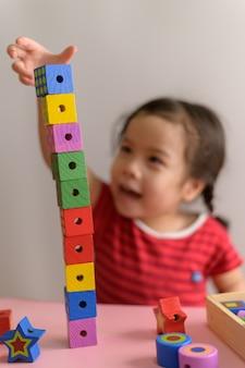 La pequeña muchacha asiática rizada disfruta jugando con los bloques de madera del juguete aislados en la pared blanca. concepto de educación y aprendizaje.