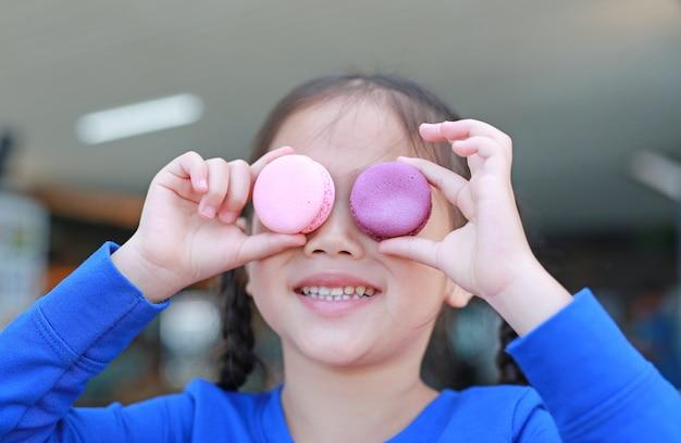 Pequeña muchacha asiática sonriente del niño que juega y que sostiene los macarrones en sus ojos.