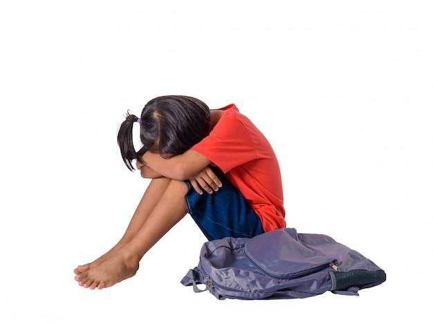 Pequeña muchacha asiática triste que se sienta en piso con la mochila aislada en el fondo blanco