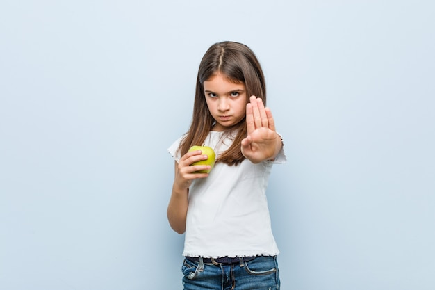 Pequeña muchacha caucásica que sostiene una manzana verde que se coloca con la mano extendida que muestra la señal de stop, previniéndole.