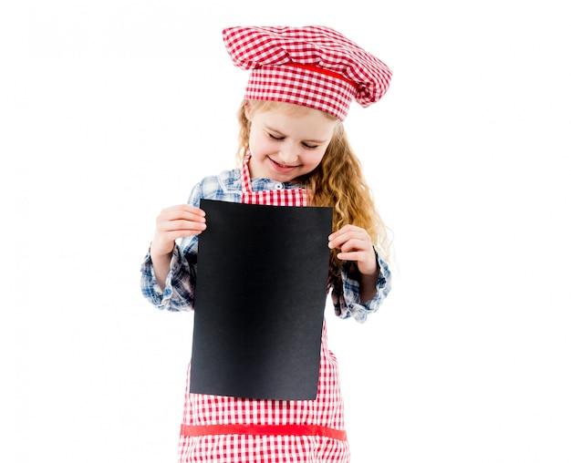 Pequeña muchacha del cocinero que sostiene el trozo de papel con el espacio libre, aislado