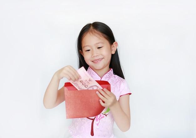 Pequeña muchacha feliz del niño asiático que lleva el vestido cheongsam tradicional rosado que sonríe mientras que recibe el paquete rojo del sobre del año nuevo chino con el dinero.