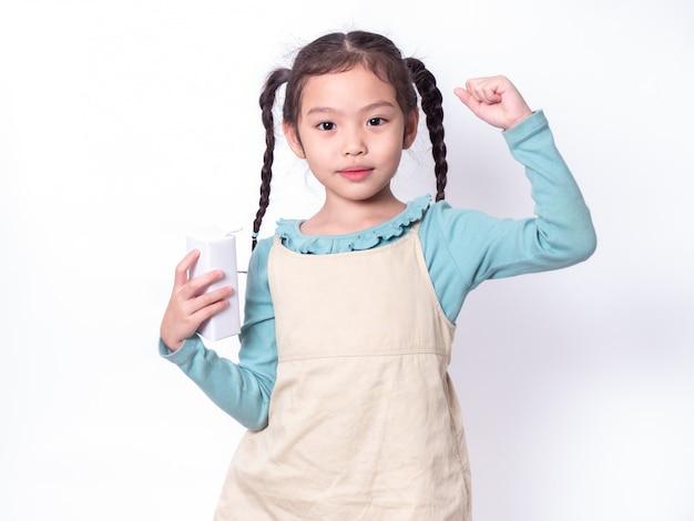 Pequeña muchacha linda asiática 6 años que sostiene y que bebe la leche del cartón de leche con la subida una mano sobre el fondo blanco.